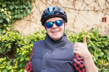 happyful cycling man in helmet and jacket, sunglasses