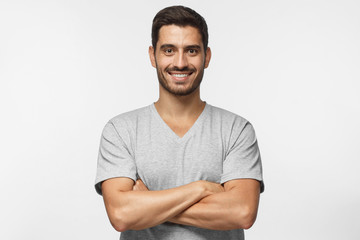 Smiling handsome man in gray t-shirt standing with crossed arms isolated on grey background