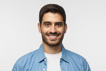Smiling handsome man in blue shirt isolated on gray background