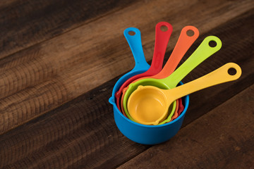 colorful measuring cups on a wooden table. Kitchen utensils concept