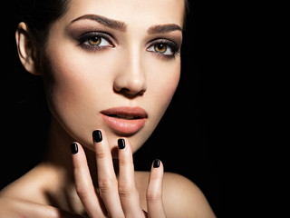 Face of a beautiful girl with fashion makeup and black nails