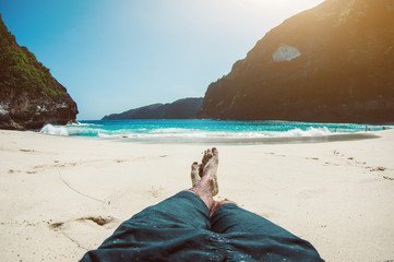 Man on vacation relaxing at the beach. Pov view