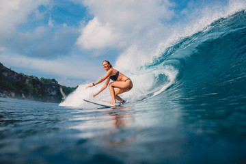 Surf girl at surfboard ride on barrel wave. Woman in ocean during surfing