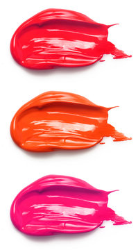 Smudged lipsticks and lipgloss isolated on white background