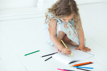 Cute little girl drawing a picture at home