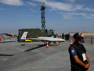 A police oficer stands next to an unmanned aerial vehicle (UAV) during Teknofest airshow at the city's new airport under construction in Istanbul