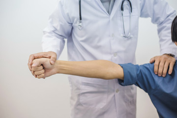 Doctor checking arm of a young man who was injured.