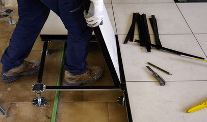 Worker install of raised floor in equipment room to spare space underground