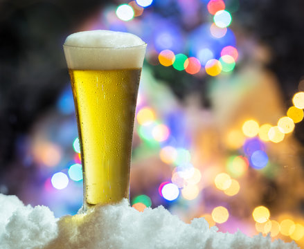 Glass of beer with magic Christmas lights at the background.