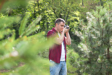 Hipster guy with retro camera outdoors in the forest