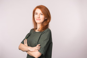 Fashion and people concept - beautiful young woman with red hair smiling over white background with copy space