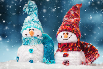 little knitted snowmans on soft snow on blue background