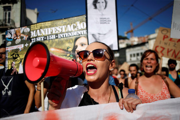 People shout slogans during a demonstration against evictions and rising of rent prices in central Lisbon