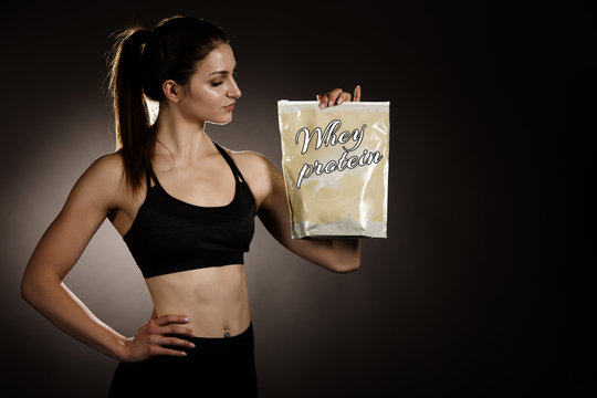 sporty woman holds a bag of whey protein