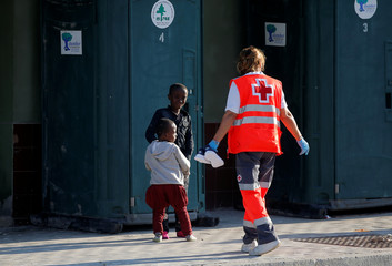 Migrant children are helped by a member of Spanish Red Cross after disembarking a rescue boat at the port of Malaga