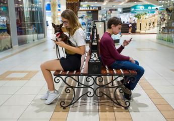 Visitors use their mobile phones as they rest in a shopping centre in Kiev