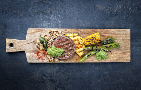 Barbecue wagyu hash burger with flatbread, pineapple and chimichurri sauce as top view on a cutting board with copy space