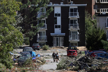 People look at the damage after a tornado hit the Mont-Bleu neighbourhood in Gatineau