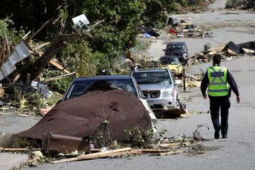 A police officer walks past damaged vehicles after a tornado hit the Mont-Bleu neighbourhood in Gatineau