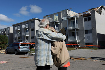 Residents embrace while looking at the damage after a tornado hit the Mont-Bleu neighbourhood in Gatineau