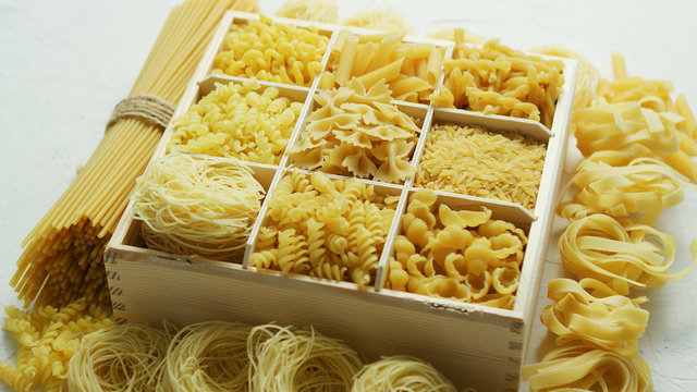 Wooden box filled with plenty of various macaroni and pasta with spaghetti in bunch