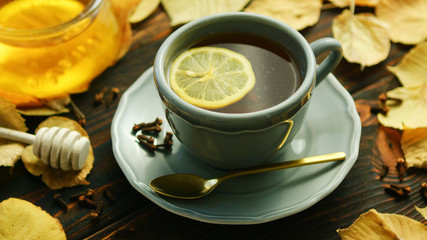 From above view of cup of hot tea with slice of lemon and bowl of honey placed near decorated with dry leaves on wooden background