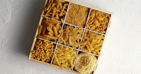 Top view of wooden box with sections filled with various types of raw macaroni and pasta on white surface