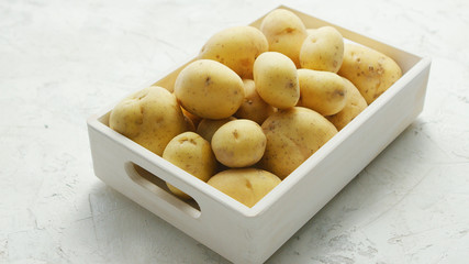 White container filled with clean fresh potatoes in soft daylight