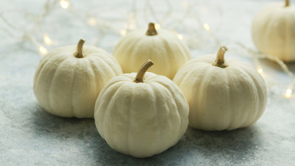 Arrangement of few white-colored fresh pumpkins on gray surface with glowing garland on background