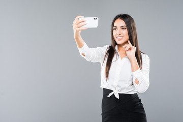 Happy businesswoman making selfie photo on smartphone or making video call over white background