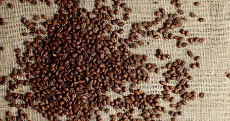 Top view of messy pile of freshly roasted brown coffee beans on textured canvas textile