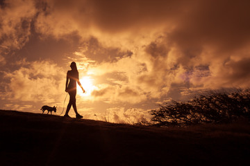 Female walking her dog outdoors at sunset.