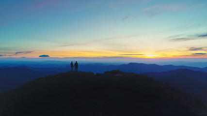 The man and woman standing on the mountain on the sunset background