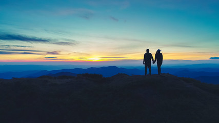 The couple standing on the mountain on the sunset background