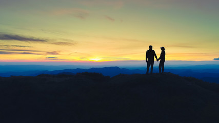 The couple standing on the mountain on the sunrise background