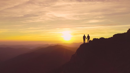 The two people standing on the mountain on the beautiful sunset background