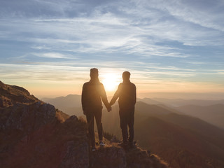 The couple standing on the mountain on the beautiful sunrise background