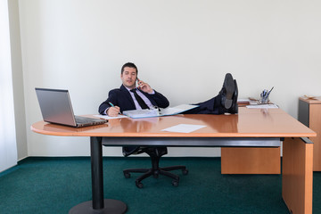 Portrait of young businessman sitting with his feet on the desk in the office writing notes while talking on the mobile phone
