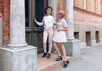Lesbian couple near the old building in the city