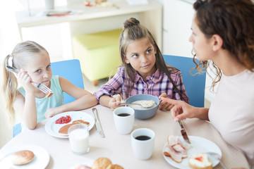 Cute little girls eating homemade meal for breakfast with their mother near by