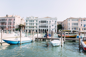 Beautiful couple in love stand on the wooden bridge on venetian canal with boats. Venice, Italy