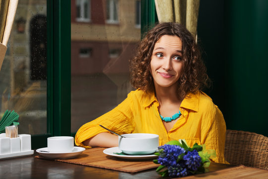 Happy young woman in yellow shirt eating a soup at restaurant