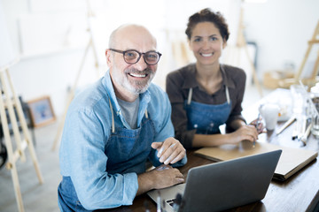 Smiling aged man and his colleague in workwear sitting by table in front of laptop in their workshop or studio
