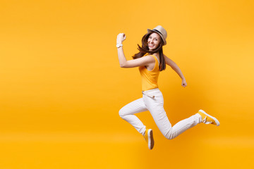 Portrait of excited smiling young happy jumping high woman in straw summer hat, copy space isolated on yellow orange background. People sincere emotions, passion lifestyle concept. Advertising area. Wall mural