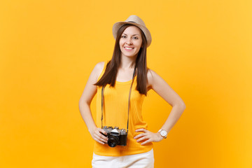 Happy traveler tourist woman in summer casual clothes, hat with retro vintage photo camera isolated on yellow orange background. Girl traveling abroad travel on weekends getaway. Air flight concept.
