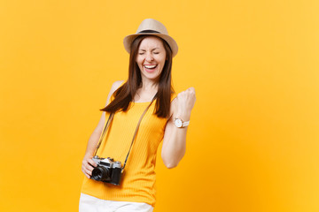 Fun tourist woman in summer casual clothes hat with photo camera clenching fists like winner isolated on yellow background. Girl traveling abroad travel on weekends getaway. Air flight journey concept