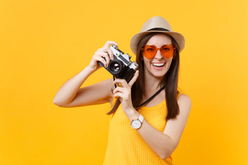 Tourist woman in summer casual clothes, hat take picture on retro vintage photo camera isolated on yellow background. Girl traveling abroad to travel on weekends getaway. Air flight journey concept.