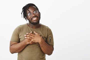 Indoor shot of cute and tender african-american male coworker in glasses and military t-shirt holding palms on chest, smiling cheerfully and gazing right with dreamy satisfied smile over grey wall