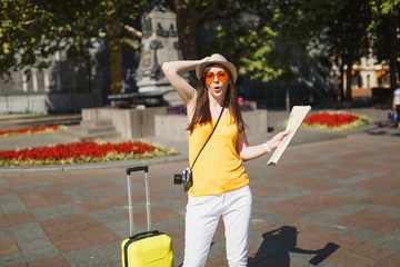 Funny traveler tourist woman in yellow clothes, orange heart glasses with suitcase city map photo camera in city outdoor. Girl traveling abroad to travel on weekend getaway. Tourism journey lifestyle.