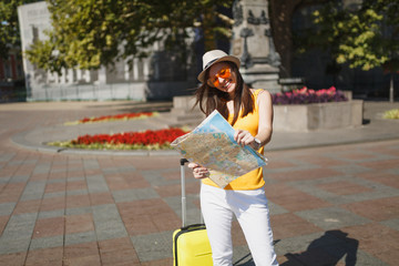 Laughing traveler tourist woman in hat, yellow clothes, orange heart glasses with suitcase hold city map in city outdoor. Girl traveling abroad to travel on weekend getaway. Tourism journey lifestyle.